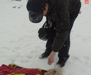 乐乐躺在地上不起来,爸爸用毛毛狗戳她的鼻子