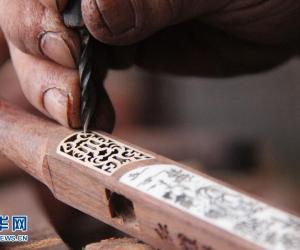 张庆瑞在雕刻二胡琴杆