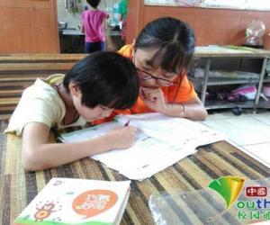 志愿者耐心辅导小朋友作业。中国青年网通讯员 张燕飞 摄